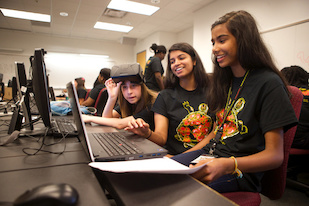 (L-R) Computer Science Connect participant Kayla Newby, teaching assistant Stacy George and participant Isha Santhosh use an Oculus Rift headset to demo the virtual reality game the two students created. Credit: John T. Consoli (Click image to download hi-res version.)