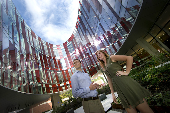 Physics students Ben Reschovsky and Katie Hergenreder stand under the ellipse of the Physical Sciences Complex at UMD. Photo: John T. Consoli